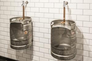 Op het toilet urineren de mannen in een opengezaagd bierfust.